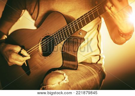 Musician with Guitar Playing Some Music. Acoustic Guitar String Instrument in Hand of Caucasian Men