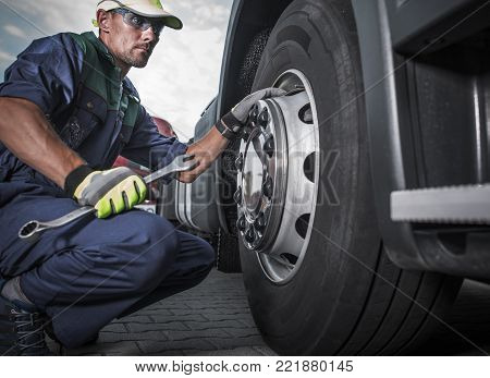 Semi Truck Wheel Maintenance. Caucasian Truck Mechanic with Large Wrench in Hand Taking Look at the Wheel in the Truck Service Center.