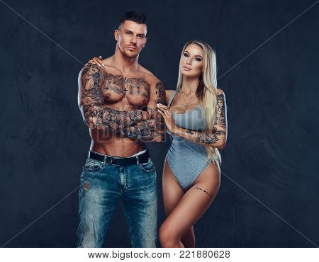 A sexy fit couple, handsome muscular man with sexy woman posing on a dark blackground.