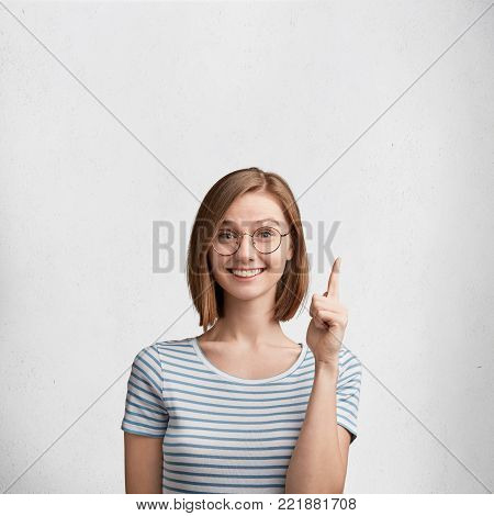 Beautiful Young Woman With Bobbed Hairstyle, Wears Spectacles And White Casual T Shirt Indicates At