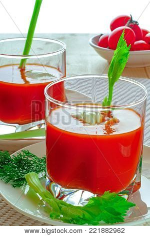 Tomato juice in two glasses.  Healthy vegetable cocktail from red ripe tomatoes, celery, dill and sour cream. Detoxification.