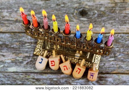 Hanukkah Chanukah Jewish holiday background with Hanukah Chanukkah menorah Judaism candelabra burning candles and traditional Dreidel game toy on wood table