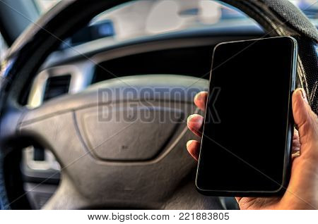 Cell phone with blank screen in hand on car steering wheel background. Black screen of phone for your inscription or pictures.