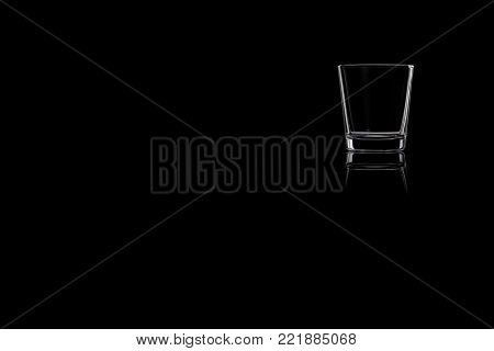 A shot glass of tequila, vodka or whiskey on a black background. Place for your text.