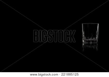 A shot of tequila, vodka or whiskey on a black background. Place for your text.