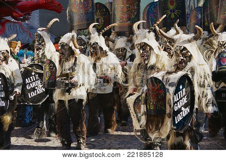 LUCERNE, SWITZERLAND - FEBRUARY 20, 2012: Unidentified people wear costumes and masks and play music at the street during Carnival in Lucerne, Switzerland.