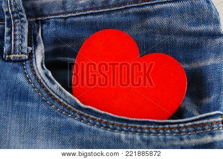 Heart - a symbol of love peeps out of the pocket of jeans trousers. The concept of the day of lovers. St. Valentine's Day