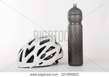 White bicycle helmet, protection of head injury on cycling and water bottle,  studio photo, isolated on background.