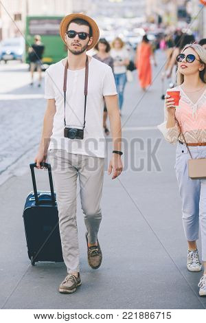 content casual couple of tourists walking in the city. family tourism. summer vacation. getting new experiences and sightseeing concept
