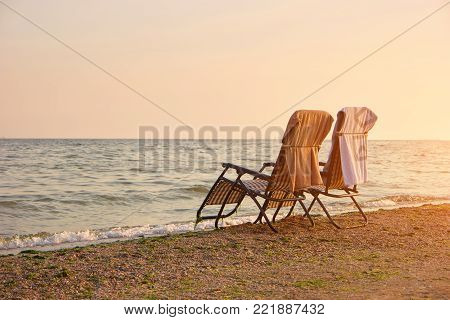 Deck chairs with towels on backrest on the seashore. Two empty deck chairs in romantic evening.