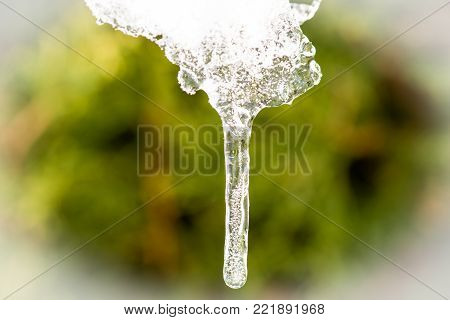 Closeup of small ice droplet hanging down in front of a blurred background. Crystalline structure visible inside the ice droplet