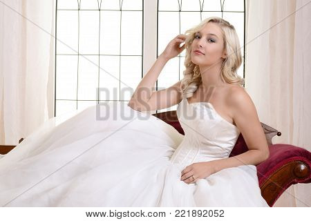 woman in white ball gown sitting on red fainting couch