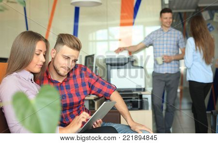 Two confident young people looking at touchpad while their colleagues working in the background