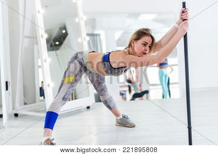 Woman doing stretching exercise for hamstrings and back leaning forward holding barbell in one hand.