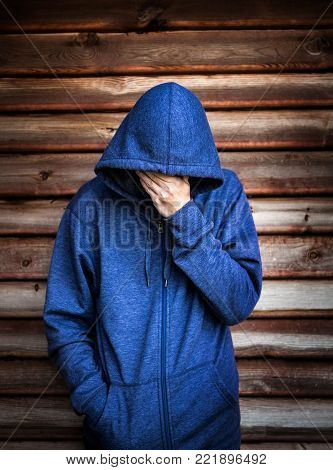 Sad Young Man in the Hoodie by the Wooden Wall