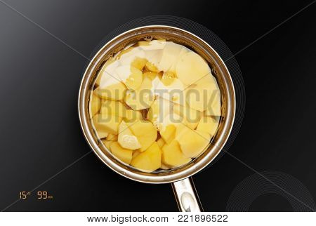 pan on the induction surface in which potatoes is cooked