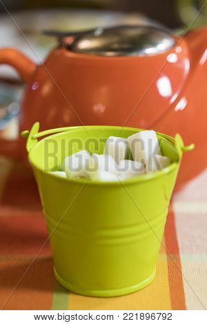 light green sugar bowl, orange teapot. close-up