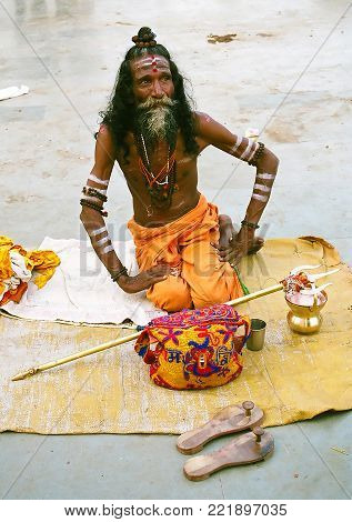Hindu Shiva sadhu in traditional dress sitting on your mat on the banks of the Ganges river in Varanasi, India - october, 20,2014: