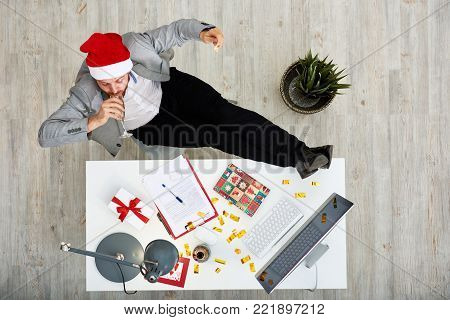 Directly above view of young white collar worker in Santas hat celebrating New Year at work: he sitting with legs on desk and drinking champagne from flute