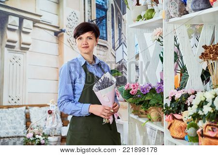 Smiling young female florist working in flower shop.Small Business Flower Shop Owner. Female sales assistant working as florist and holding bouquet with lavender. Salesman is standing with of flowers.
