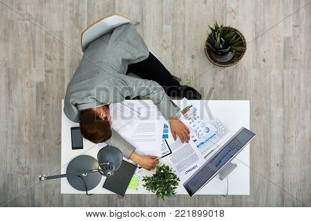 Tired young white collar worker taking nap while sitting at office desk covered with documents, directly above view