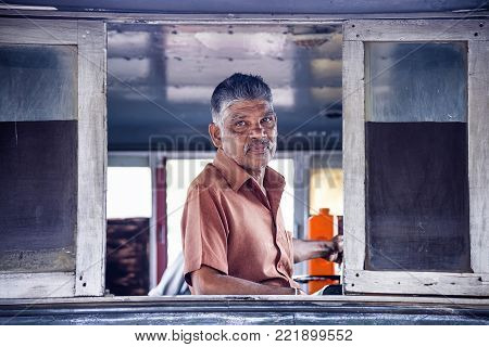 Kandy, Sri Lanka - August 19, 2017: A train driver inside locomotive at Kandy's station. Sri Lanka Railways (SRL) is the only rail transport organization in the country