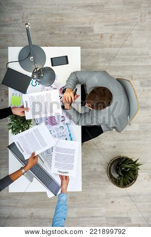 Directly above view of busy dark-haired entrepreneur sitting at office desk while his colleagues passing him several contracts for signature