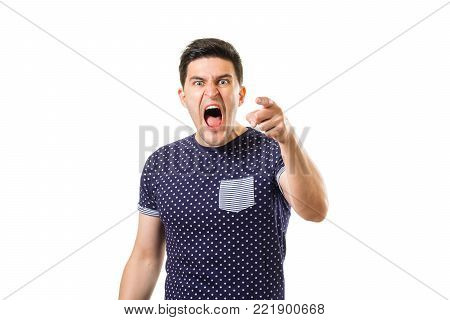 Some young angry brunet guy pointing at you by finger and screaming loudly isolated on white