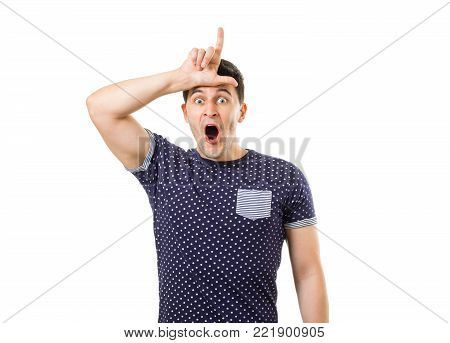 Handsome young guy with funny expression on face showing loser gesture by hand