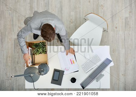 Moving to new office: dark-haired manager putting his belongings in cardboard box while standing at wooden desk, directly above view