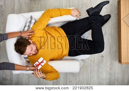 Smiling bearded man wearing mustard sweater sitting on cozy armchair while his girlfriend passing him gift box, directly above view