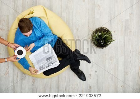 Bearded young man sitting on cozy beanbag chair and reading newspaper while his girlfriend passing him cup of fragrant coffee, directly above view