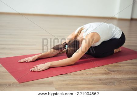 Woman doing the Child's pose on red yoga mat. Balasana