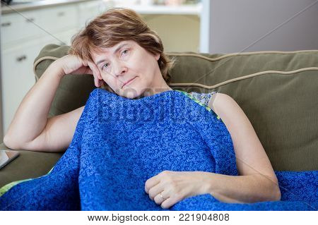 horizontal close up image of a sad and lonely caucasian woman with brown hair and eyes  sitting on couch resting with her head in hand with a blanket around her
