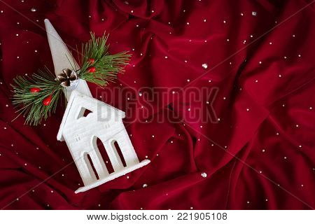 horizontal image of a small ornamental white glass church lying on a deep red cloth background with room for test.