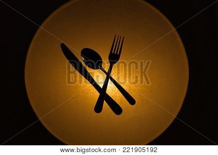 horizontal image of a kitchen knife and spoon and fork silhouetted by a warm golden circular light with a black background.