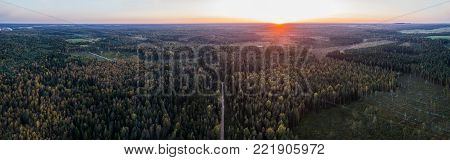 Aerial view of road among autumn forest in Estonia. Panorama. Sunset.