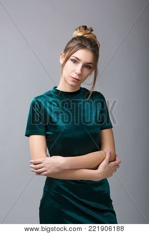 Portrait of beautiful woman with makeup, hairstyle and natural freckles on her face in green dress posing and looking at camera on gray background. Studio shoot poster