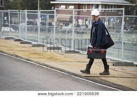 Leiden, Zuidholland/The Netherlands - September 28th 2017: a young caucassian male wearing a white hardhat and boots and his bags to his construction work