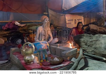 BABUGHAT, KOLKATA, WEST BENGAL / INDIA - 9TH JANUARY 2018 : Indian Hindu Sadhu , sitting with Holy ashes applied all over his body. Shot agsint holy smoke.