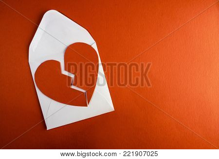 A break up valentine envelope letterwith a broken paper heart ontop of it against a red paper background template