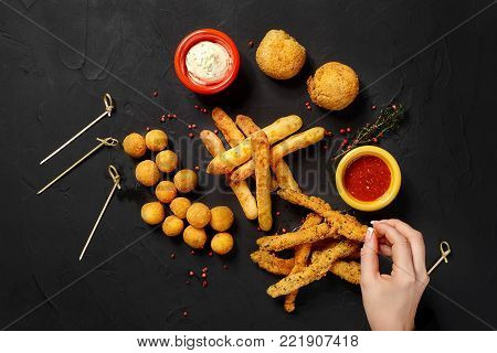 Mushrooms in batter, cheese balls, cheese sticks and cheese rings in batter, on black background, with herbs, sauce, ketchup and pepper. Top view. Copy space. Still life