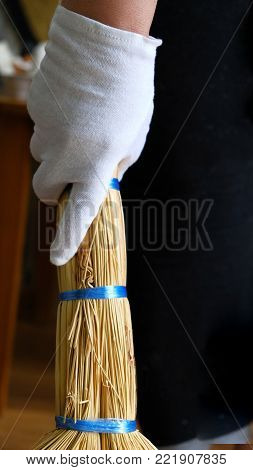 A hand in a white glove holds a broom for Cleaning and sweeping room. Vertical photo