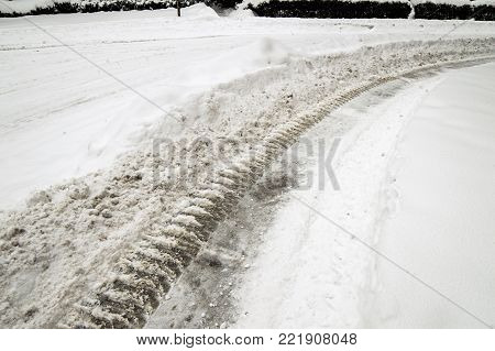 Winter driving and snow storm conceptual image with room for copy space closeup car tire tracks in deep snow low angle view curvy road in deep snow conceptual insurance, winter driving safety and accident prevention background in bad weather snowstorm