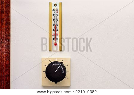 The conditioner regulator and room thermometer located on the wall of gray color.