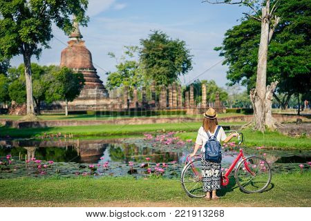 Young woman traveler travelling into Big buddha statue at Wat Si Chum or Wat Sri Chum temple in the Sukhothai Historical Park contains the ruins of old Sukhothai, Thailand, UNESCO world Heritage Site.