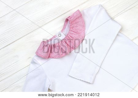 Beautiful white pajama on wooden background. Pink fine pattern collar. New girls' clothing collection.