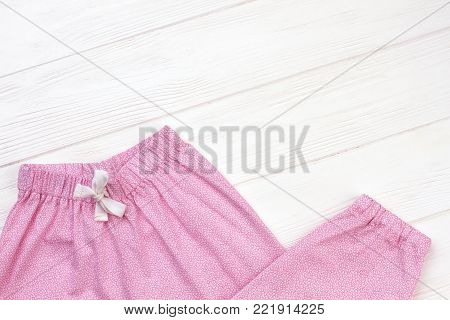 Girls' sleepwear on wooden background. Pants made of pink fabric with fine pattern. Elastic waistband and drawstring.