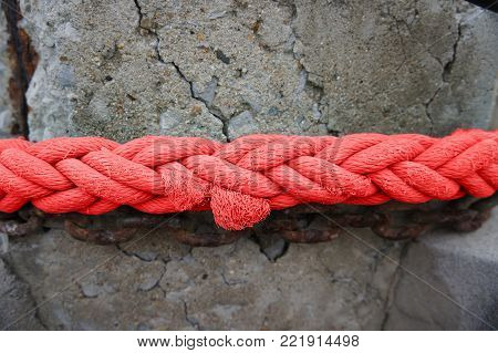 Close-up of Red rope, tie fasteners with cracked cement sticks.