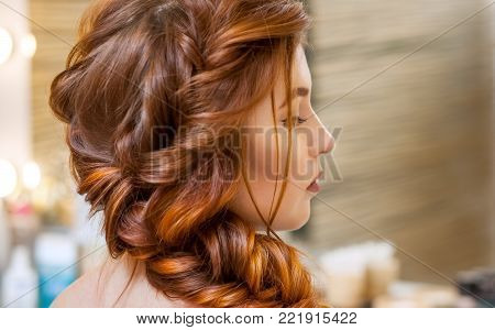 Beautiful, With Long, Red-haired Hairy Girl, Hairdresser Weaves A French Braid, In A Beauty Salon. P